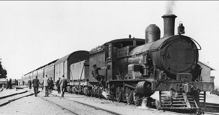 A Commonwealth Railways G-class locomotive with a westbound Trans-Australian Express train, Tarcoola, South Australia. Photo ca. 1925. (Wikimedia Commons photo)